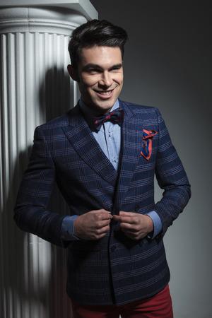cerrando negocio: Hombre de negocios feliz sonriendo a la c�mara mientras se cierra la chaqueta.