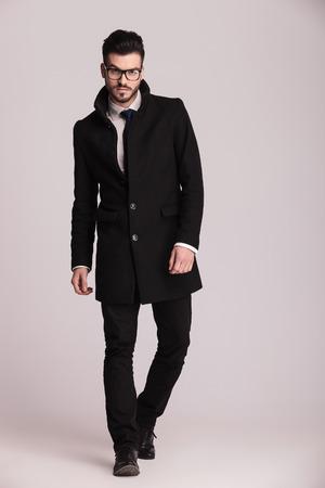 カメラに向かって歩いて長い黒いコートを着ているハンサムな若いビジネス人。 写真素材