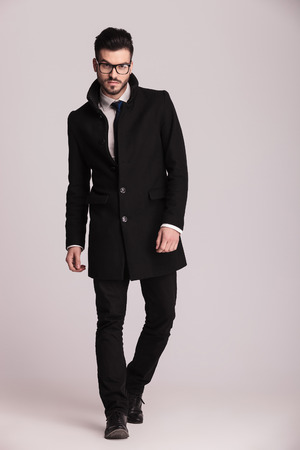 bata blanca: Hombre de negocios joven hermoso que desgasta un abrigo largo negro caminando hacia la c�mara. Foto de archivo