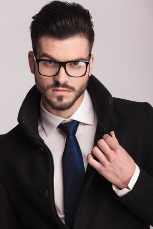 man face close up: Close up picture of a handsome business man fixing his collar while looking at the camera. Stock Photo
