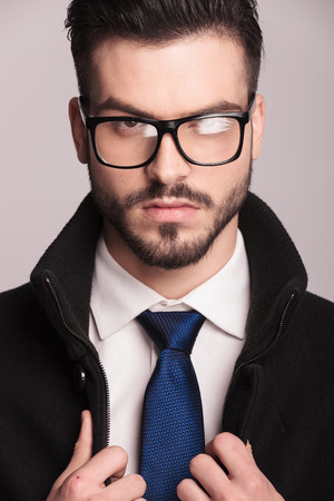 man face close up: Close up picture of a elegant business man wearing glasses. He is fixing his coat while looking at the camera.