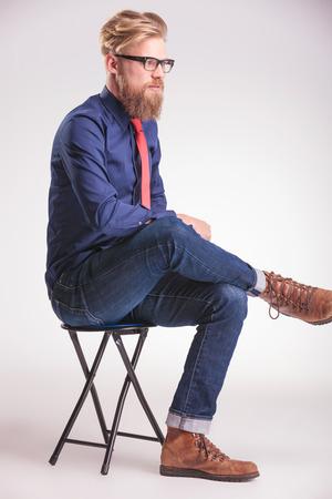 hombre rojo: Side imagen vista de un joven casual sentado en un taburete de la celebraci�n de sus piernas cruzadas mientras mira a la c�mara, pensando.