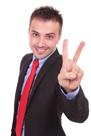 peace sign: Happy business man smiling at the camera while showing the victory gesture with his fingers. Stock Photo