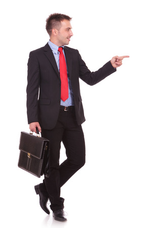 bod: Attractive young business man pointing at something to his left while holding a black briefcase.