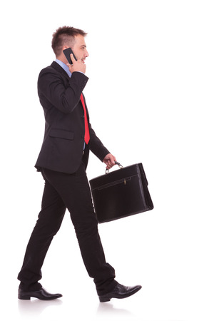 Side view picture of a handsome business man walking on studio backgound while talking on the phone. Archivio Fotografico
