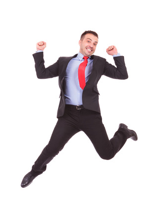 jump suit: Happy young business man jumping with his hands in the air, celebrating a good deal. Stock Photo