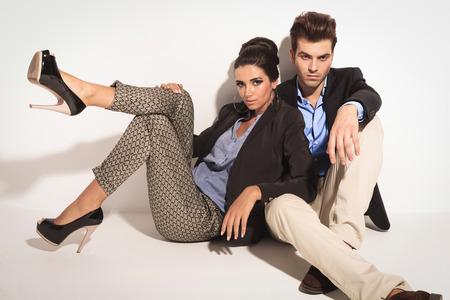 poses de modelos: Apuesto joven casual sentado en el suelo mientras que su novia está inclinando en él.