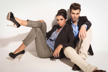 male fashion: Handsome young casual man sitting on the floor while his girlfriend is leaning on him.