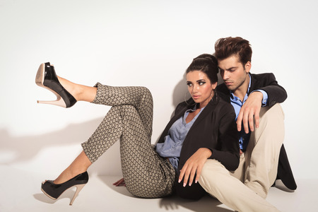 near side: Fashion couple sitting on the floor together, looking away from the camera. The woman is leaning on ther man. Stock Photo