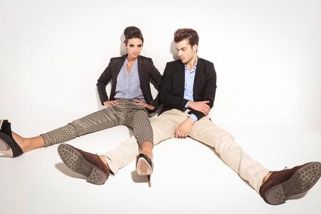legs apart: Foto de cuerpo entero de una joven pareja de moda relaja en fondo del estudio con sus piernas separadas. Foto de archivo
