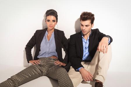 jambes �cart�es: Attrayante jeune femme de la mode assis sur le sol avec les jambes �cart�es pendant que son copain est assis � c�t� d'elle, regardant vers le bas.