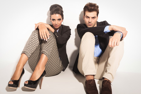 knees up: Fashion couple sitting on studio background with the knees up, holding their hands on them. Stock Photo