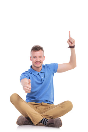 casual young man sitting on the floor with his legs crossed and pointing upwards while also showing the thumb up gesture and smiling for the camera. isolated on white photo
