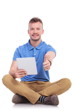 posing  agree: casual young man sitting on the floor with his legs crossed and showing the thumb up gesture to the camera while holding a tablet and smiling. isolated on white
