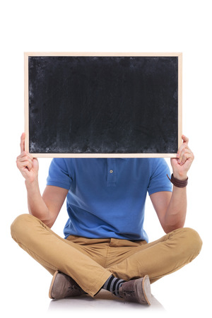 picture of a casual young man sitting on the floor with his feet crossed while holding a small blackboard in front of his face. on a white backgroun photo