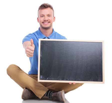 picture of a casual young man sitting on the floor with his feet crossed while holding a small blackboard and showing the thumb up gesture. on a white background photo