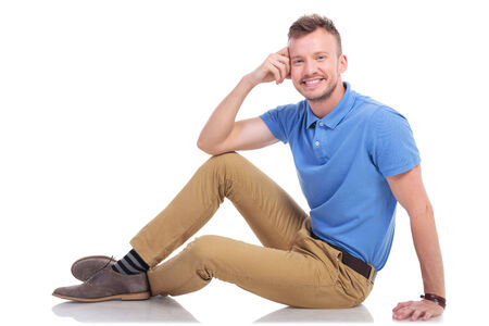 confortable: full length picture of a casual young man posing on the floor with a smile on his face and a hand at his head. on a white background Stock Photo