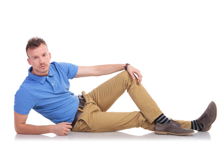 sitting on the ground: full length picture of a casual young man lying on the floor and looking into the camera with a serious expression on his face. on a white background Stock Photo