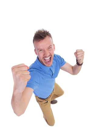 top angle view: top view of a casual young man cheering while looking into the camera. on a white background