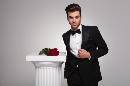 man in tuxedo: Elegant young business man fixing his tuxedo near a white column with a roses on top of it. Stock Photo