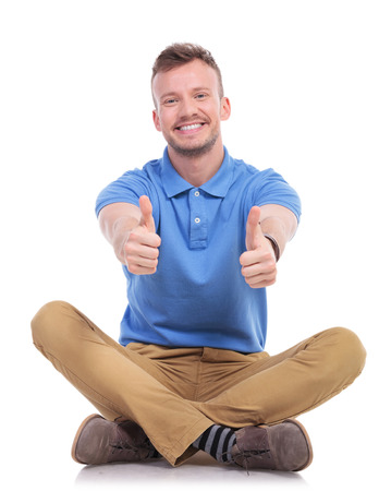 casual young man sitting on the floor with his legs crossed and showing thumbs up gesture with both hands while smiling for the camera. isolated on white photo