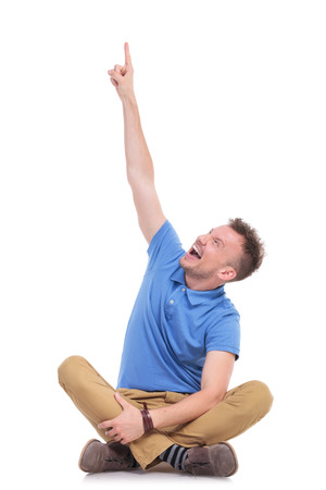 casual young man sitting on the floor with his legs crossed and pointing at something above him with excitement. isolated on white photo