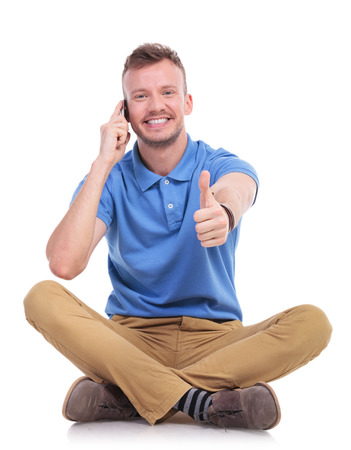 casual young man sitting on the floor with his legs crossed and talking on the phone while showing the thumb up gesture and smiling for the camera. isolated on white photo