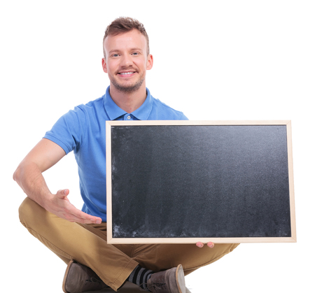legs folded: picture of a casual young man sitting on the floor with his feet crossed while holding a small blackboard and pointing at it. on a white background Stock Photo