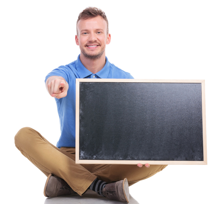 picture of a casual young man sitting on the floor with his feet crossed while holding a small blackboard and pointing at the camera with a smile on his face. on a white background photo