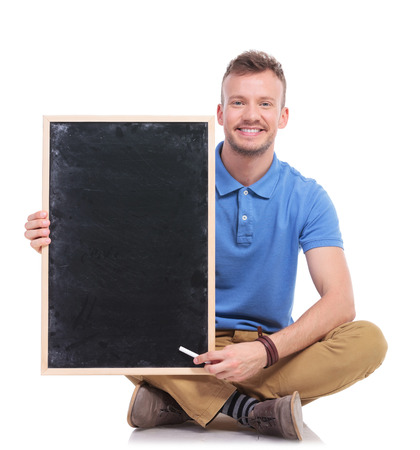 picture of a casual young man sitting on the floor with his feet crossed while holding a small blackboard and pointing at it with a piece of chalk. on a white background photo