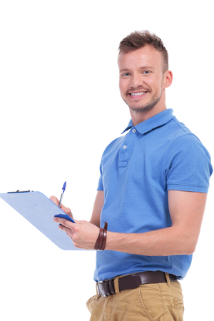 filling out: portrait of a casual young man holding a clipboard and taking some notes while smiling for the camera. on a white background