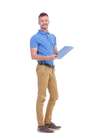 full length portrait of a casual young man taking some notes on a clipboard and smiling for the camera. on a white background Stock Photo
