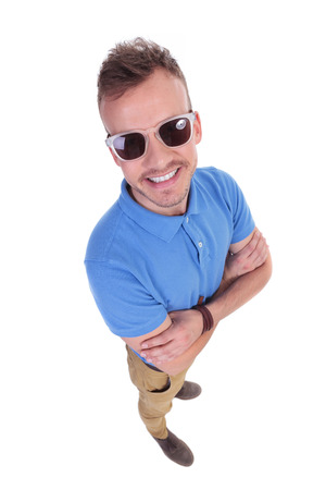 top angle: top view of a casual young man smiling with his hands folded. on a white background