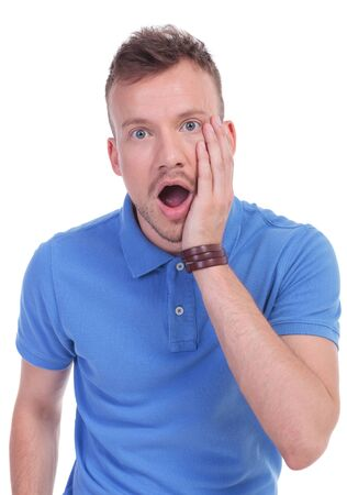 picture of a young casual man with a shocked expression on his face. isolated on a white background photo