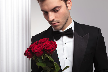Elegant business man looking at a red roses bouquet, posing near a white column. photo