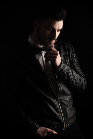 man looking down: Young business man looking down while holding his hand to his chin, on dark studio background. Stock Photo
