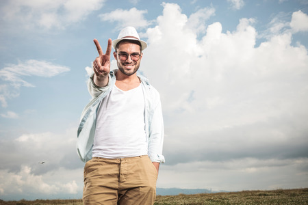 field glass: Happy young fashion man posing outdoor, showing the victory sign while holding one hand in his pocket. Stock Photo