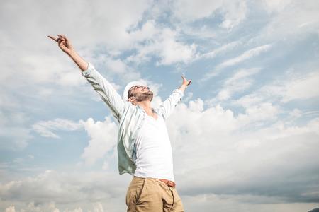 hombre con sombrero: Vista lateral de un hombre joven feliz disfrutando del buen tiempo, mirando hacia arriba y la celebraci�n de sus manos en el aire. Foto de archivo