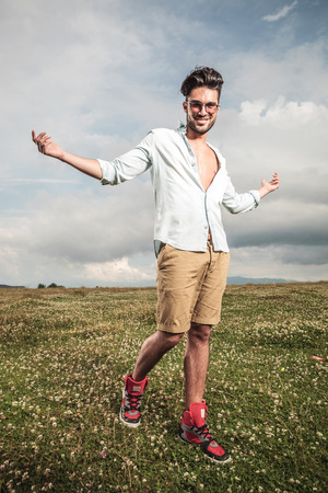 field glass: Young man walking on a field with flowers with his arms open, smiling and looking at the camera.