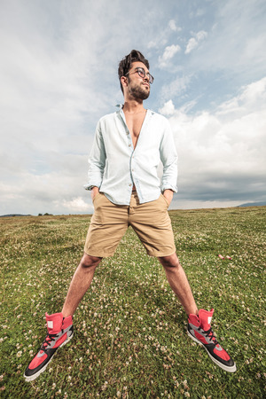legs apart: Handsome man posing on a field of grass with his legs apart, holding his hands on pockets, looking away.