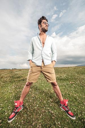 legs apart: Hombre hermoso que presenta en un campo de hierba con las piernas separadas, con las manos en los bolsillos, mirando a otro lado.