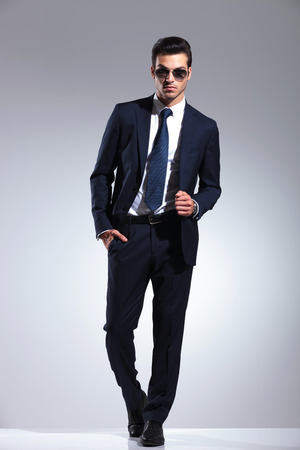 Full length picture of a elegant business man posing on grey studio background, holding one hand in his pocket while pulling his jacket. Imagens
