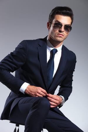 cerrando negocio: Hombre de negocios hermoso que se sienta mientras que el cierre de su chaqueta, mirando a la c�mara.