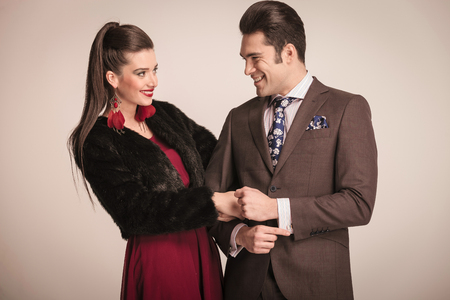 romantically: Happy young fashion couple laughing while looking at each other. The woman is holding the man by the arm. Stock Photo