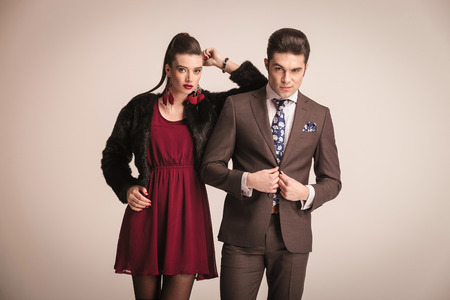 romantically: Elegant fashion woman leaning on her lover while he is closing his jacket.