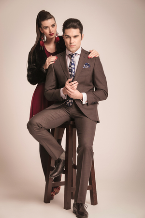 sensual couple: Elegant fashion woman standing behind her lover while he is sitting on a stool.