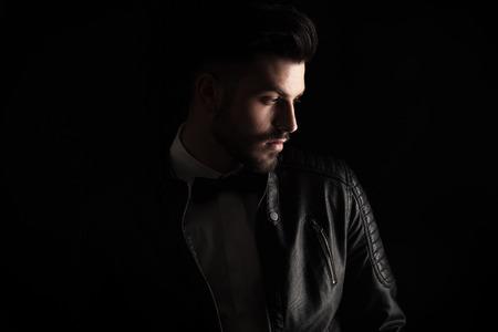 chaqueta: Hombre de negocios atractivo mirando hacia abajo a su lado en el estudio de fondo oscuro. Foto de archivo