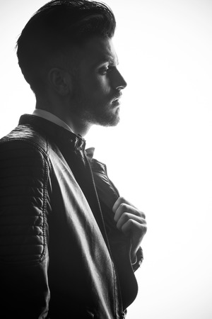 Side view image of a young business man pulling his leather jacket.