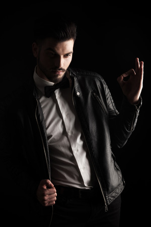 Attractive young business man pulling his leather jacket while showing the ok sign. photo