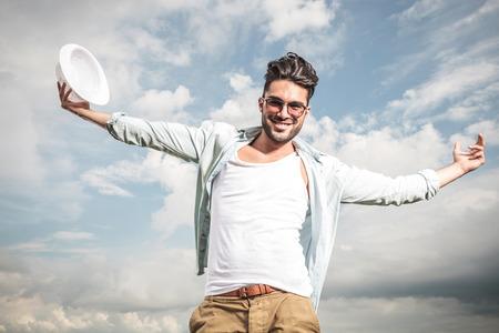Glücklicher junger Mann posiert im Freien mit den Armen öffnen, genießen das sonnige Wetter. Standard-Bild - 36152829